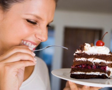 Smiling woman eating cake